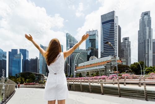 Girl with raised arms on skyscrapers background