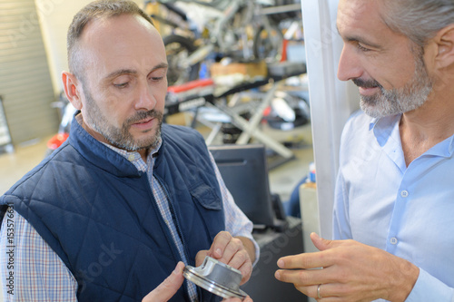Mechanic showing part to customer Poster