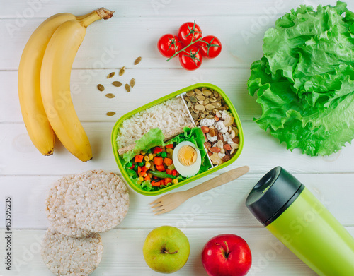 Lunch box filled with rice and mixed vegetables and nuts near thermos mug © lithiumphoto