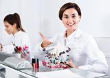 Female manicurist showing lacquer color schemes