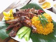 Chamorro beef and chicken barbeque meal with yellow rice in banana leaves Authentic Chamorro favorite cuisine of beef and chicken barbeque served with yellow rice, cucumber and lemon slices.