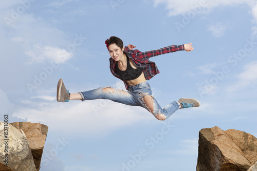 Woman jumping over the gap at blue sky