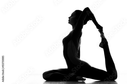 ddc9da94082a Loving sport. Silhouette of a flexible sporty woman practicing yoga indoors  isolated on white