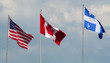Canada, USA, and Quebec flags waving in the wind cloudy day