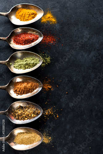 Spices and herbs in spoons and space for your text
