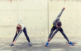 close up of couple stretching on city street