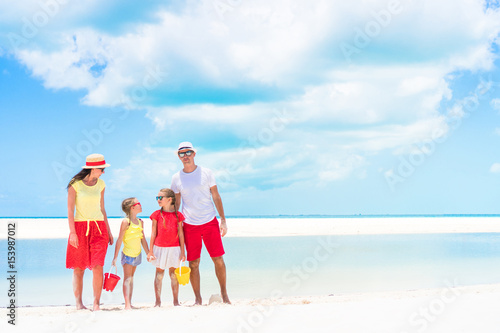 Family of four on a tropical beach Poster