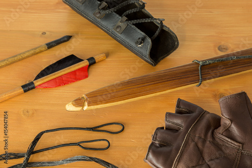 Fotobehang Jacht Conceptual image of archery. A wooden long bow, arrow tip, arrow back feather, gloves, arm guard protection and bow strings.