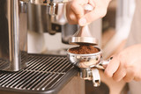 Barista holding tamper to press ground coffee in a portafilter for making coffee from espresso machine - 154069458