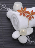 Spa setting with candle, towel ,orchid, ,salt on mat