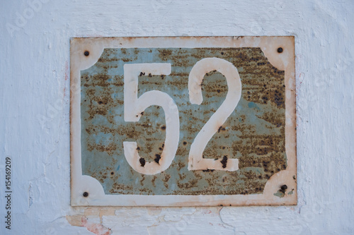 Poster Very old rusty house number 52 plate on cracked white facade