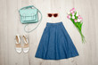 Jeans skirt, glasses, white shoes, handbag and a bouquet of tulips. Fashionable concept. Wooden background.