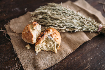 Bread loaf breaked in half, wheat on burlap cloth