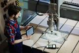 Factory worker operating cutter machine using digital tablet in workshop - 154199277