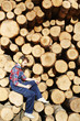 Side view portrait of lumberjack using smartphone on break from work on timber cutting site sitting on tree trunks