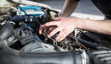 The master repairs under the hood of the car