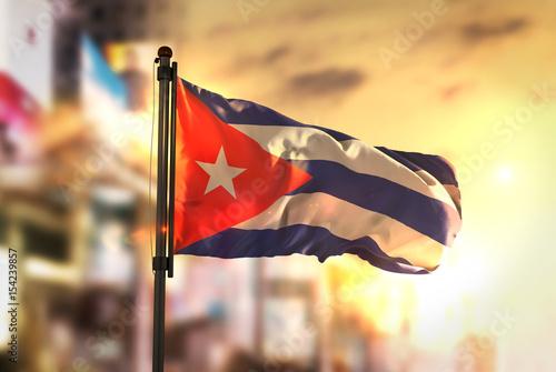 Cuba Flag Against City Blurred Background At Sunrise Backlight