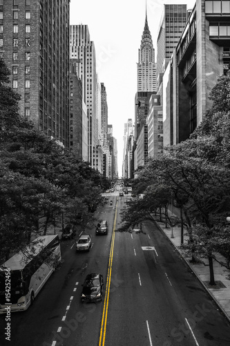 Endless streets of Manhattan New York skyscraper cars yellow lane marking black and white