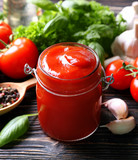 Composition of ketchup in jar and ingredients on wooden background, closeup