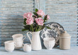 Pink roses in a white enameled pitcher, vintage crockery on blue wooden rustic background. Kitchen still life in vintage style. Flat lay