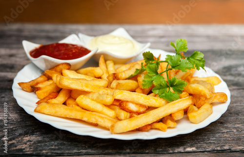 Poster French fries with tomato sauce, mayonnaise and parsley on wooden table