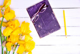 Glasses on a book, next to a bouquet of yellow irises