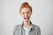 Naughty teenage girl with ginger hair and freckles misbehaving, sticking out her tongue at camera as a sign of disobedience, protest and disrespect. Human emotions, reactions, feelings and attitude