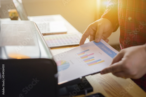 Businessman analyzing investment charts and business plan with printer. Accounting,Business People Planning Strategy Analysis Office Concept,vintage color © Have a nice day
