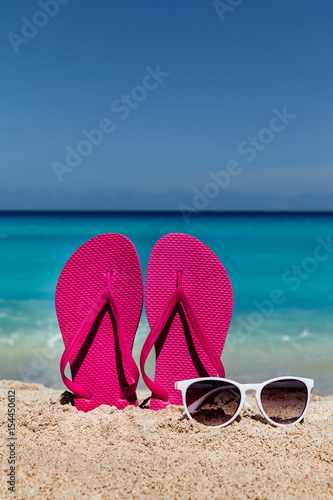 1afe621b7795 Flip flops with sunglasses on the sandy ocean beach