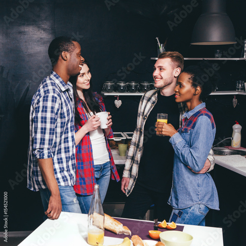 Company of friends in kitchen together Poster