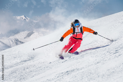 Female skier on a slope in the mountains - 154538841