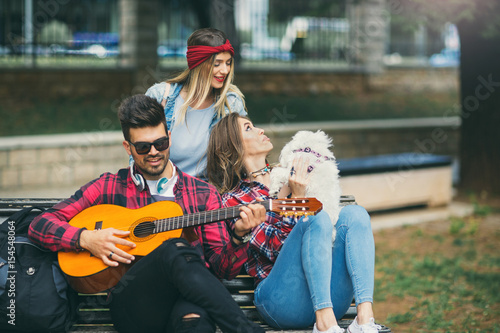 Poster Friends in the park having fun playing guitar