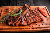 Sliced medium rare grilled steak on rustic cutting board with rosemary and spices , dark rustic wooden background, top view