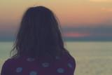 Lonesome girl watching the dawn / dusk over sea / ocean horizon. - 154615645