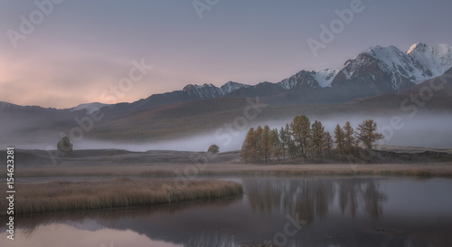 Foto op Canvas Lavendel Misty autumn morning, a picturesque mountain lake on a background of snow capped mountains