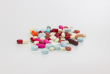 Multicolor antibiotics tablets and capsules on white background.