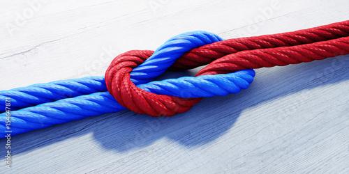Kreuzknoten mit rotem und blauem Seil auf weißem Holz  - 154647871