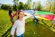 Girl playing parachute together with her friends