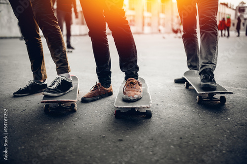 Group of friends skateboarders rest on the street and skateboard