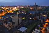 Abandoned ironworks factory in the dark with a shining city in the background