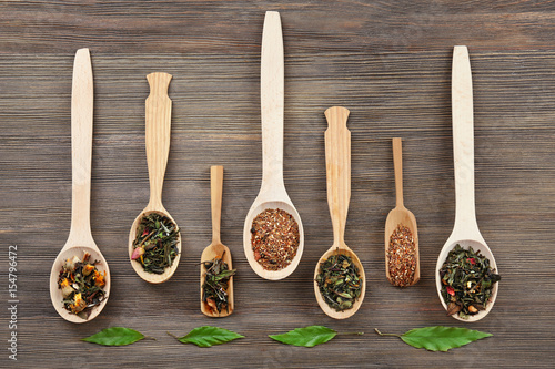 Black tea in spoons on wooden background