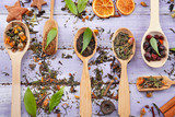 Dried tea in spoons with herbs on wooden background, top view