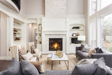Beautiful Living Room in New Luxury Home with Fireplace and Roaring Fire. Large Bank of Windows Hints at Exterior View - 154812627
