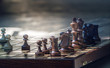 Wooden chess pieces on a wooden chessboard outdoor at the sunny day - 154935836
