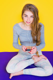 Beautiful young yogini woman sitting down in lotus pose on purple mat and listening to relaxing music from her phone