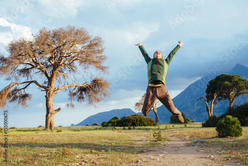 Póster Man jumping into the air over beautiful sunset landscape