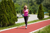 Young woman is jogging on sunny day.