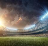 soccer stadium with illumination and green grass on sunset