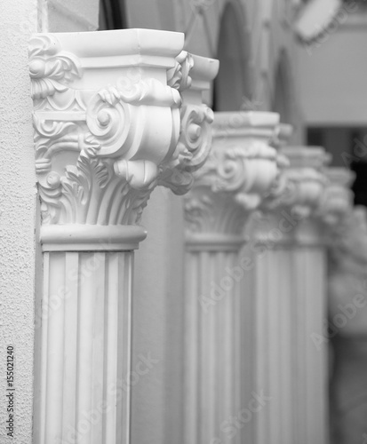 White plaster sculpture of a row of ornate columns on a mason wall. A number of gypsum columns. - 155021240