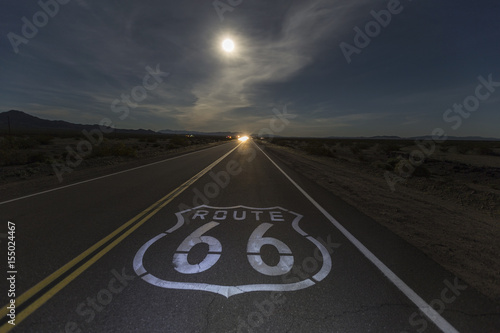 Route 66 sign with full moon and oncoming headlights in the California Mojave desert Poster